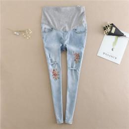 Modne dopasowane dżinsy damskie ciążowe z efktownymi przetarciami na nogawkach i haftowanymi kwiatkami regulowany pas w talii